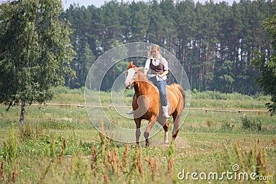 Beautiful blonde woman riding horse bareback