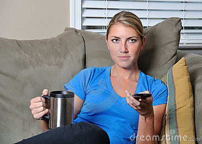 Beautiful blonde woman watching TV with remote
