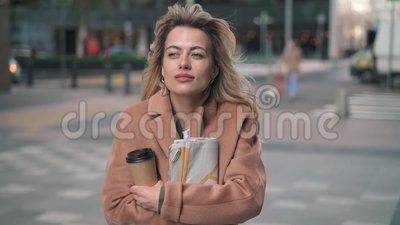 Blonde woman with coffee shivering with cold in fall street. Beautiful blonde woman wearing beige coat, holding a cup of coffee and a newspaper shivering with stock video footage