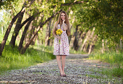 Beautiful blonde woman with yellow flowers outdoor