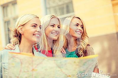 Beautiful blonde women with map in the city