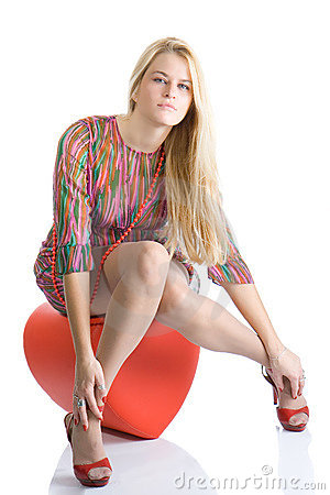Beautiful blondy sitting on red heart and posing