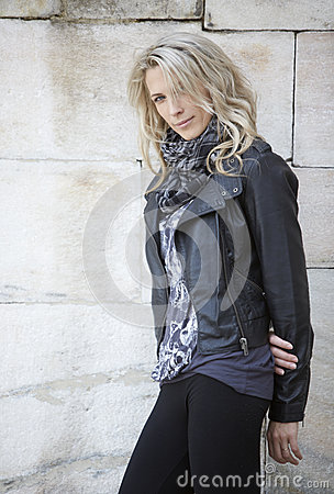 Beautiful blue eye blonde woman, stand against a wall
