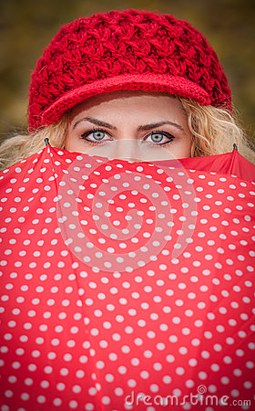 Beautiful blue eyes over colorful umbrella. Attractive blonde girl with red cap looking over red umbrella outdoor shoo