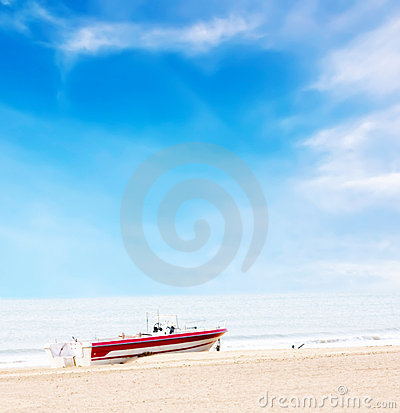 Beautiful boat on beach under blue sky and clouds