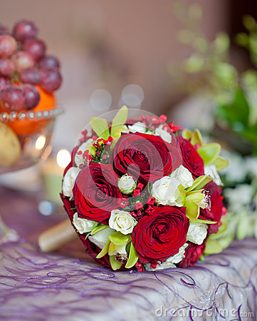 Beautiful bouquet of rose flowers on table. Wedding bouquet of red roses. Elegant wedding bouquet on table at restaurant