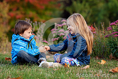 Beautiful boy and girl in a park, boy giving flowers to the girl Stock Photo