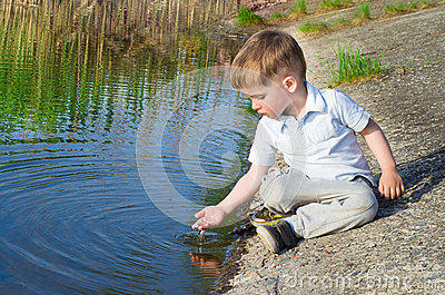 Beautiful boy pours water from the palm