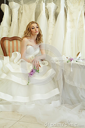 Beautiful bride on background of wedding dres