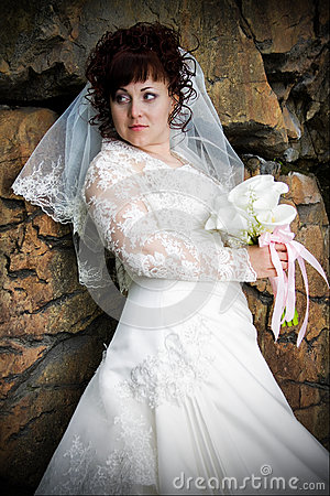 Beautiful bride with a bouquet, amid rough walls