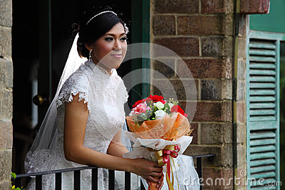 Beautiful bride with bouquet on terrace