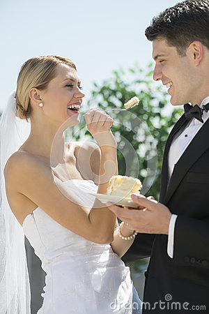 Beautiful Bride Feeding Wedding Cake To Groom
