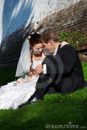 Beautiful bride and groom sit on the grass