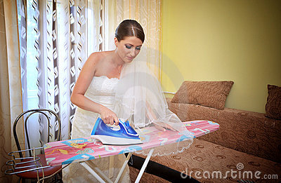 Beautiful bride ironing