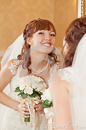 Beautiful bride  looking through mirror