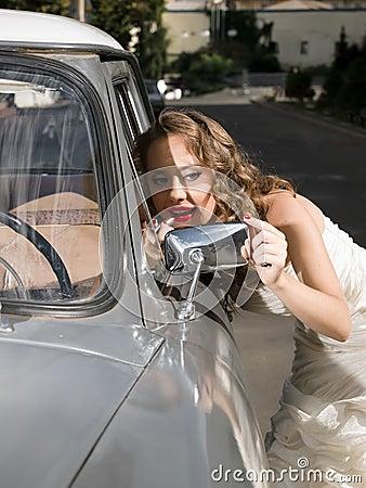 Beautiful bride near the car