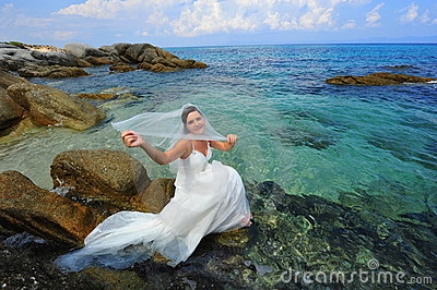 Beautiful bride sitting over the crystal clear sea