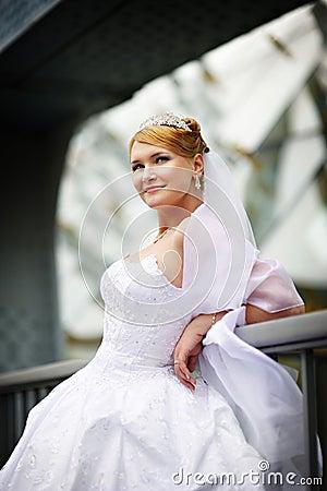Beautiful bride in a wedding dress near parapet