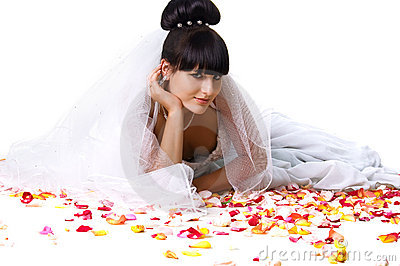 Beautiful bride in a white dress with rose petals