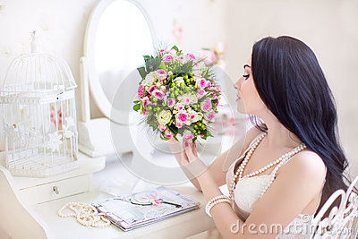 Beautiful bride in a white dress with a wedding bouquet of pink