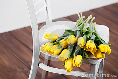 Beautiful bright yellow tulips in Still Life lying on antique white Chair
