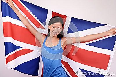 Beautiful British girl smiling holding up the UK flag.