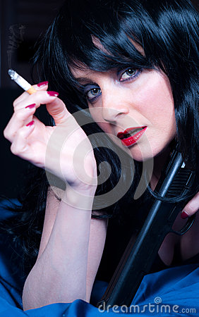 Beautiful brunette girl with cigarette and gun