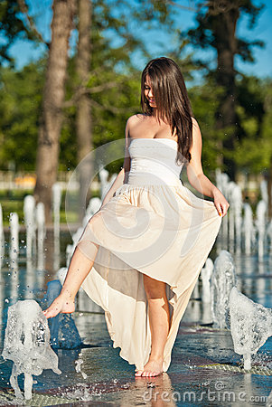 Beautiful brunette girl playing at  water fountain