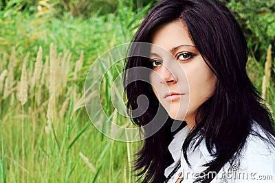 Beautiful brunette in a green lea