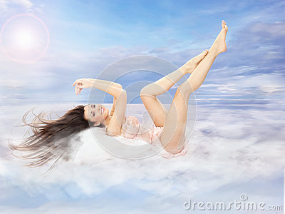 Beautiful brunette lying on clouds