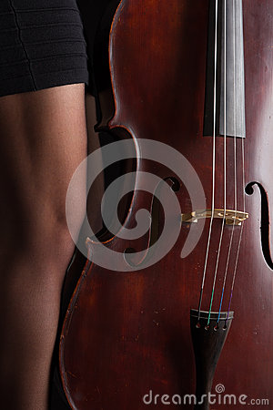 Beautiful brunette playing cello with selective light in black d Stock Photo