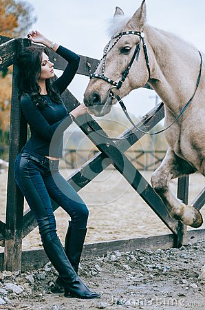 Free Beautiful Brunette Posing With A Horse In The Autumn Afternoon At A Country Ranch. Lifestyle Photo. Fashion Photo. Horseback Ridin Royalty Free Stock Photo - 108306515
