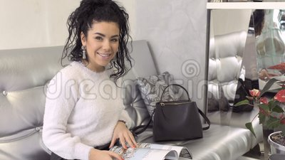 Beautiful smiling brunette with magazine sit at sofa. Beautiful brunette read magazine at the sofa. The woman holds journal in hands and looks in camera with stock video