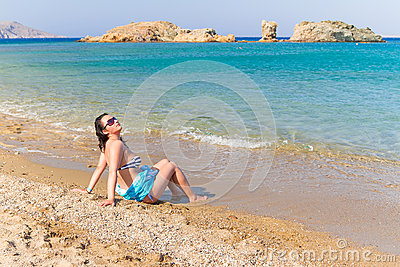 Beautiful brunette at relaxation on the beach of Crete