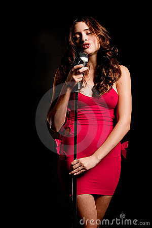 Beautiful brunette singer singing with microphone