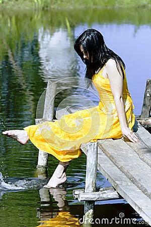 Beautiful brunette splashes water
