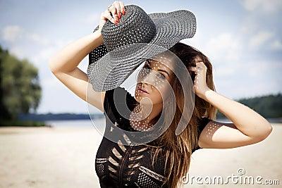 Beautiful brunette woman in black dress bikini