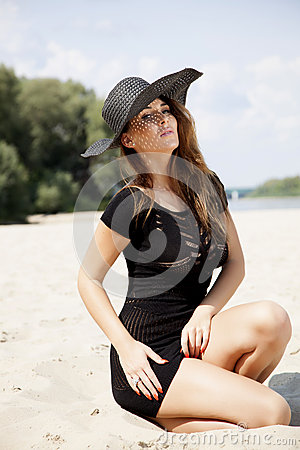 Beautiful brunette woman in black dress bikini