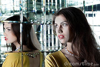 Beautiful brunette woman near mirror