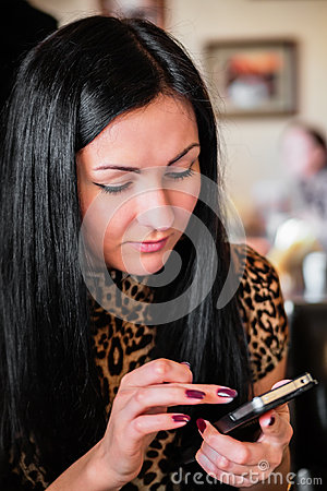Beautiful brunette woman looking at mobile phone