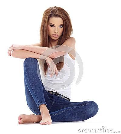 Brunette woman sitting on the floor . Studio shoot.