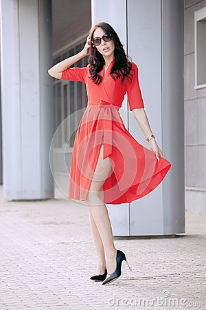 Free Beautiful Brunette Young Woman In A Red Dress, In Black High-heeled Shoes, Sunglasses, Walking Along The Street. Fashion Royalty Free Stock Image - 100394866