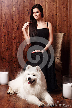 Free Beautiful Brunette Young Woman Long Black Dress With A Snow-white Dog Samoyed Husky Studio In Shades Of Brown Candles Royalty Free Stock Photography - 52422077