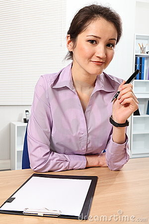 Beautiful business woman at her desk thinking