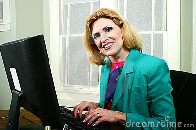 Beautiful Business Woman Smiling And Typing On Computer
