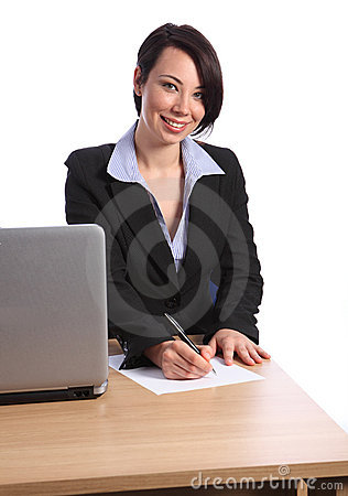 Beautiful business woman writing at office desk