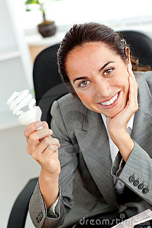 Beautiful businesswoman holding a light bulb