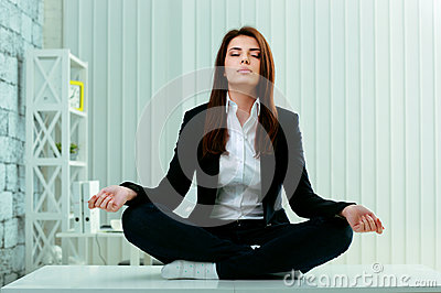 Beautiful businesswoman meditates on the table