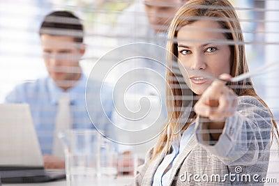 Beautiful businesswoman peeping through blind