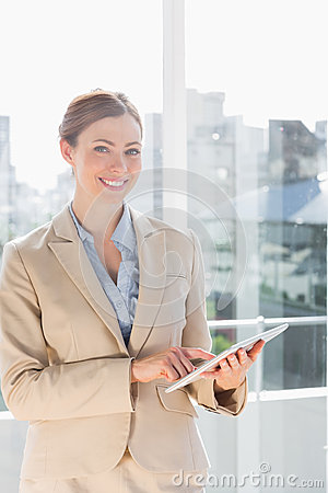 Beautiful businesswoman using her tablet pc and smiling at camer